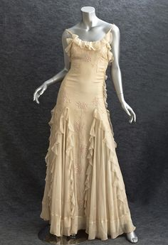 chiffon evening gown, 1930s - 2 separate layers of ivory silk chiffon over a paneled satin-&-chiffon under layer. Outer layer is hand embroidered w/ pink silk floss flowers; form fitting shape to hip, skirt has exaggerated sweep w/ bias cut panels; ruffles outline the panels. The cost of additional yardage was significant, so this was made for a wealthy woman. Each layer is meticulously finished & closes on the side w/ small hooks & thread loops. $ 1,400