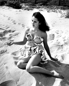 Elizabeth Taylor,15, photographed by Bob Landry showing off, frilly two-piece bathing suit on beach (1947).