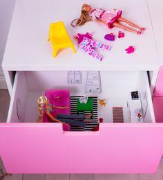 Pinkin laatikon sisus ylhäältä päin katsonnuna. Laatikossa nukke istuu olohuoneessaan. Laatikoston päällä on toinen nukke ja tuoli.