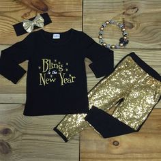 """Black top with """"Bling In The New Year"""" written in gold glitter. Gold sequined leggings WITH or Without accessories!!! >Cotton/Spandex >True To Size Order the size she normally wears everyday. (If unsu"""