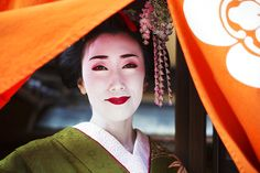 A woman dressed in the traditional geisha style, wearing a kimono with an elaborate hairstyle and floral hair clips, with white face makeup with bright red lips and dark eyes lifting an orange curtain, Japan