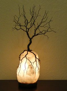 Description: This beautiful bare tree and lighted salt rock sculpture is a one of a kind piece. No two can ever be created the same. The tree is made with many strands of antique brass and dark colored wire. This creates a beautiful realistic appearance and lots of detail. The tree sits atop this lighted rock with the roots grabbing onto it to hold it lightly in place. Tree is not glued down. Salt rock lamp sits on a wood base and has a power cord with on/off switch. Glows beautifully i...