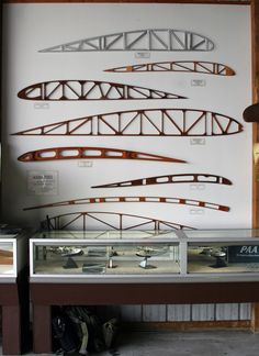 This display shows the evolution of wing rib construction and cross-sections.  From top to bottom are: Piper J-3 Cub (1939), Franklin Sport 90 (1929), Star Cavelier (1929), Ryan WL1 (1926), Curtiss JN-4 (1918), Halberstadt (D.1), and Wright Model B (1911).