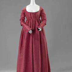 Gown, anonymous, c. 1790 - c. 1810 silk, l  At the end of the 18th century the wide skirts became narrower, and the waistline was raised to under the bosom. The narrow sleeves were so long that they extended to the middle of the hand. They were set in far at the back to a typical lozenge-shaped panel, the shape of which is emphasized by ornamental stitching in a colour that contrasts with the red silk of the dress. http://hdl.handle.net/10934/RM0001.COLLECT.51029