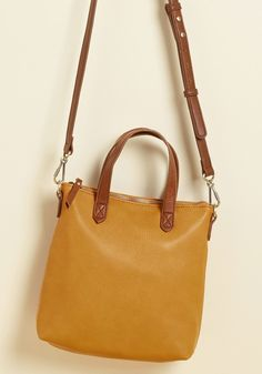 <p>With this goldenrod bag in your wardrobe, you'll excitedly oblige any and every opportunity to show it off! From lunch reservations to solo city excursions, this pouch-style purse - with its brown accents, dark gold hardware, and faux-leather fabric - lends itself as the ensemble encouragement to get you movin'.</p>