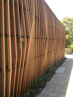 Wood slat walls with glass behind under roof overhang to office entrances on west side