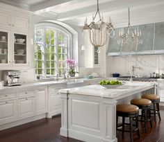 Island posts    O'Brien Harris: Modern French kitchen with white kitchen cabinets paired with marble countertops and ...