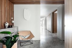 A modern entryway with a leather chair and wood slat wall that flows onto the ceiling.