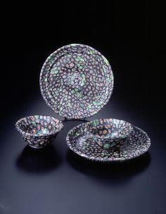 https://flic.kr/p/854a1P | A Set of Roman Mosaic Glass Patella Cups and Shallow Dishes | Mosaic glass, ca. 1st century B.C.E./C.E.  Cups and dishes cast from mosaic fragments aligned in a mold. The two dishes are almost the same size and shape, with bent walls and flat bases. The bases have attached feet made of dark green glass. The interior surface of the base has a single thin groove cut into its center and two concentric grooves further out. The central groove has its small raised…