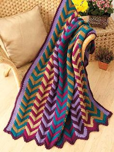 """Panels of chevrons in a jazzy combination of neutral and bold colors give a traditional design to an art nouveau look. This e-pattern was originally published in the February 2013 issue of Crochet World magazine. Size: 42"""" x 57"""". Made with worsted-weight yarn and sizes H/8/5mm and J/10/6mm hooks.Skill Level: Intermediate"""