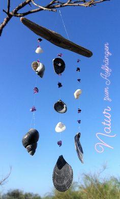 Mobile mit Fundstücken vom Strand, Muscheln und Schnecken, schwarz-weiß mit lila Schmucksteinen
