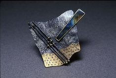 Brooch by Harold O'Connor. Reticulated silver with pierced and roller printed bimetal. Bezel set labrodorite.