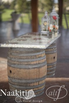 Cocktail hour: As a table, we used out plexi glass top over our two wine barrels w/ lanterns and bud vases. The inside is filled with rose petals. #cocktail #wedding #roses #altf #naakitifloral #winebarrel