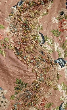 Detail of the decoration with fly-fringe, robe à la Française (sack dress), France, 1710-1774. Salmon-coloured silk brocade with floral design.