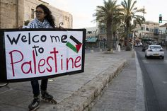 A young woman holds a sign at a demonstration commemorating Land Day in Jaffa, March 30, 2014.