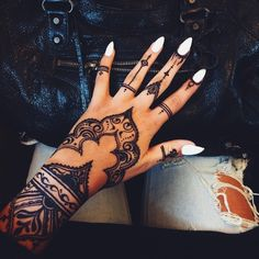 tatouage henné noir, mains féminins au vernis blanc avec dessins temporaires à design ethnique