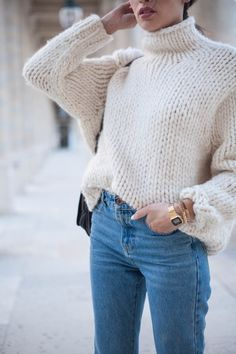 A simple cream white knit turtleneck sweater with light wash jeans.