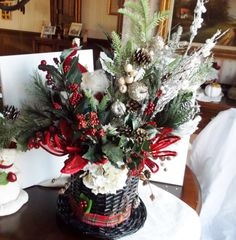 Only at White Squirrel Gifts A Snowman hat holds graceful floral stems, berries and holly to make his new year bright. A Santa Claus is tucked in neatly against all the flora and fauna. Pictures show. Snowman Hat, Reindeer, Christmas Wreaths, Christmas Tree, Stems, Picture Show, Squirrel, Floral Arrangements, Berries