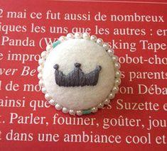 くるみボタンのブローチ☆ほっこりと白いフェルトに、グレーの刺繍糸で王冠のワンポイント刺繍。パールとターコイズで上品度もアップ♪sizeサークル3.5cm  ハンドメイド、手作り、手仕事品の通販・販売・購入ならCreema。