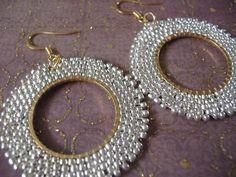 Espectaculares aretes de perlas con muy bonito satinado plata metálico 11,0 rocallas con anillo de oro, el lazo y earwires. El gancho francés resultados earwires y lazo son son bañados en oro 14kt.  Estos pendientes muy livianos son hechos a mano por mi con cada grano minúsculo tejido individualmente. Miden 2 pulgadas totales incluyendo la earwires. Los aros son de 1,5 pulgadas.  Ideal para prendas de día y sorprendentemente elegante para la noche.  Todos los artículos son hechos a mano y…