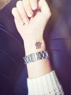 tatouage simple au poignet, patte de chat noire avec un petit coeur