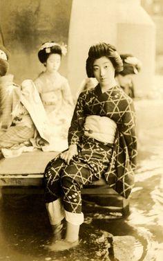 "Geiko Tomigiku by the Kamogawa (1920)  ""Geiko (Geisha) Tomigiku sitting on a platform under the Shijo Ohashi (Shijo Bridge), wading in the waters of the Kamogawa (Kamo River) in Kyoto, around the late 1910s or early 1920s."" (source)"