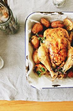 Roasted chicken on top of a wooden table with a grey tablecloth