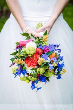 Bruidsboeket in kleurrijke multi-color tinten met blauw ridderspoor, rode en witte dahlia, afgewerkt met oranje en zachtgroene accenten.
