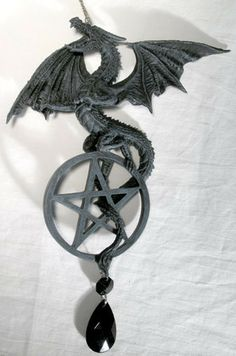 "This hanging ornament portrays a fierce eastern dragon in flight through the air above your bed, its tail wrapped around the pentagram with dangling black stone it clutches in its claws. This dreamcatcher is made of cold cast resin with exacting detail. The sinew of its wings and the tiny barbs of each scale are clearly visible. Measuring a span of 7"" between its wingtips and 9"" in length down to the bottom of the black crystal beneath it, this dreamcatcher comes on a 9 1/2"" chain for $17.95"