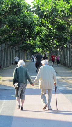 Little old lady and a little old man (with a cane) holding hands on a walk down the sidewalk