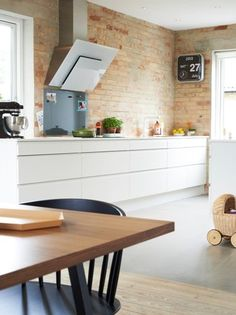 white modern kitchen and raw brick wall