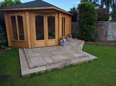 A seating area outside a new summerhouse using sawn rainbow sandstone and sett edgings by SilverBirch Gardens Ltd