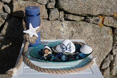 """Beach and Butterfly é uma decoração da ArteNatis constituída por:  - Uma vela decorativa azul;  - Uma decoração em forma de estrela-do-mar;  - Uma corda de sisal;  - Um elemento em vidro em forma de concha, preenchido com pot-pourri azul, um conjunto de 3 """"mini troncos"""", uma pedra branca decorada com uma pintura realizada a mão de uma borboleta e uma decoração em forma de concha."""