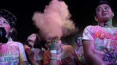 """- Estudante sopra pó colorido durante o """"Miles Smiles"""", evento para arrecadar fundos para ONG que trata crianças com lábio leporino, em Bangcoc, na Tailândia. Foto: Lillian Suwanrumpha / AFP"""