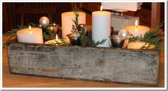 chippy old seed box for holidays / table centerpiece / white candles / cut evergreen / pinecones and Christmas ornaments.