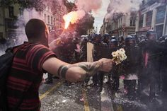 A man holds a bouquet of flowers and a torch as he faces riot police during a demonstration against the government's planned labor reform, on May 26, 2016 in Lyon, central eastern France. The French government's labor market proposals, which are designed to make it easier for companies to hire and fire, have sparked a series of nationwide protests and strikes.  share_image: >-   GettyImages-534434682.jpg big_three_section: >-   News emotion_section: