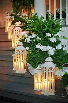 This outdoor staircase decor look works so well because the white flowers pick up the metal whiteness of the lanterns, which in turn have different heights to create interest with the tea light votive candles