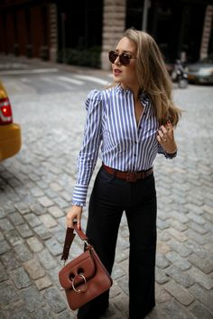Blue + white stripped button down shirt with puff shoulder & high ruffled neckline, wide-leg retro dark-wash jeans + wide statement brown leather belt, large tortoise shell vintage sunglasses, brown leather satchel bag. Nyc Fashion, Fall Fashion Trends, Work Fashion, Autumn Fashion, Fashion Outfits, Office Outfits, Casual Outfits, Office Attire, Work Outfits