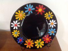 Ten inch black circle, multi-colored flowers.