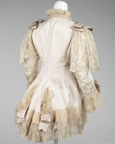 Dressing Jacket1885  Featured, is an excellent example of a dressing jacket from the period of the late 1880s to the mid-1890s. The combination of the ribbon and lace add an elaborate touch which is very typical of fashions from this time. Prior to this, lingerie and dressing wear was much simpler, but beginning in the 1880s the idea of luxury in fabrics and decoration became popular.- The Metropolitan Museum of Art