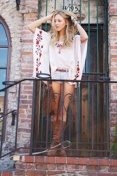 Fashion blogger, Shea Marie, wearing tan boots, jean shorts, and a bohemian embroidered top. That fringed purse is fab.