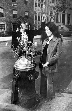 "John Lennon & Yoko Ono, the ""flower hydrant"" outside their Greenwich Village apartment, 1971."