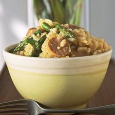 Making risotto in the microwave is less labor-intensive than stovetop cooking that requires constant attention. Sausage and asparagus turn this into a one-dish meal.