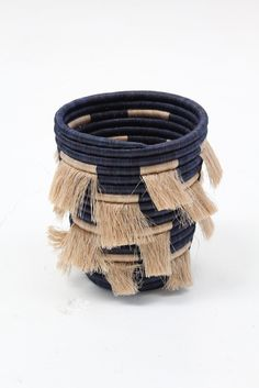 "Hand woven sweetgrass, locally grown natural fibers, tea & navy contrasting colors, 8"" x 9"" tall Made fairly in Rwanda. All profits fund educational training programs for the women."