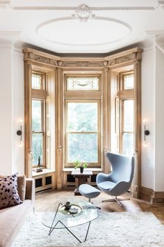 Brooklyn brownstone living space with large windows, and modern baby blue armchair
