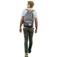 A young man walking away in green pants and a blue shirt. He has a backpack and could be a graduate student.