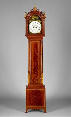 "John Seymour (1771–1848) - Tall Case Clock. Mahogany, Mahogany Veneer, Maple with White Pine. Works by James Doull and Dial possibly Painted by John Ritto Penniman. Boston, Massachusetts. Circa 1805-1810. 111-3/4"" x 21-1/4"" x 9-3/4"" (283.8cm x 54cm x 24.8cm). Metropolitan Museum of Art."