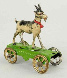 Vintage German tin litho toy goat on platform with gold-washed wheels.