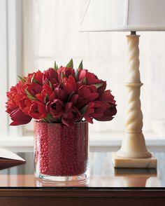 Let your sweets inspire the color scheme of your centerpiece. The intense red of these tulips -- 'Red Nova' and 'Pallada' -- pairs perfectly with the spicy cinnamon candies lining the vase.