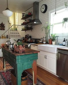 Classic white kitchen gets a pop of color with green island, bright rug, and open shelves.
